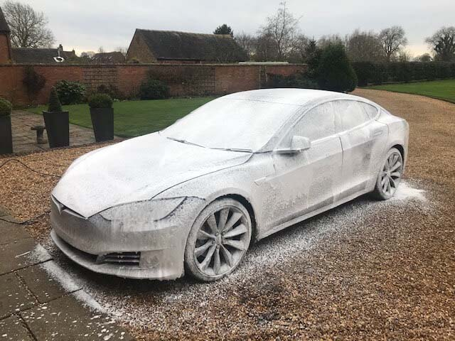 A Tesla covered in snow foam